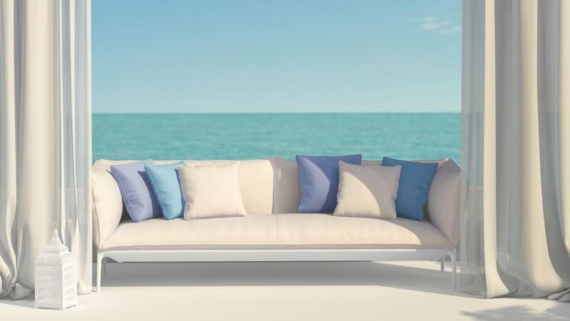 Beige Couch mit blauen Kissen zwischen zwei Vorhängen auf einer Terrasse direkt am Meer