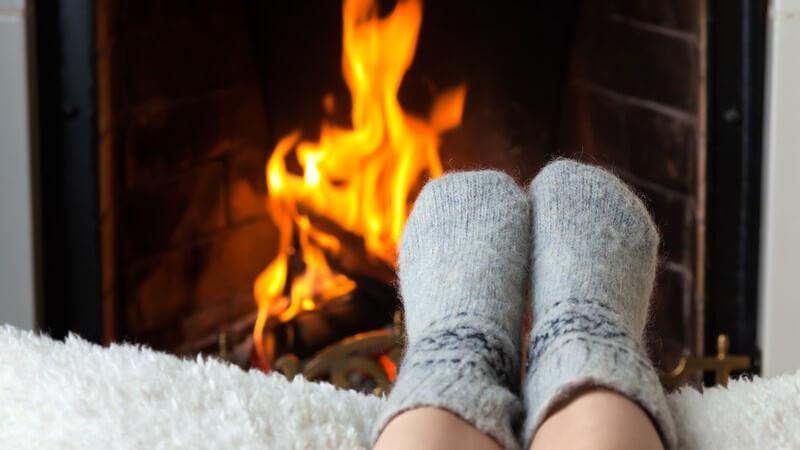 Füße eines Kindes mit warmen Socken, im Hintergrund Kaminfeuer