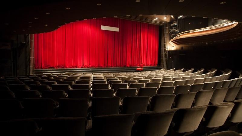 Blick in ein leeres Theater mit geschlossenem, roten Vorhang