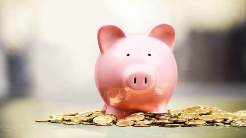 Rosa Sparschwein in einem Haufen von Geldmünzen