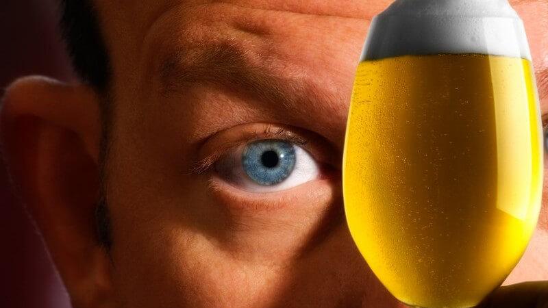 Mann hält ein frisch gezapftes Glas Bier vor sein Gesicht