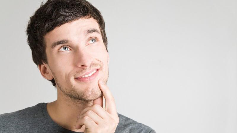 Mann schaut nachdenklich nach oben, Zeigefinger an Kinn