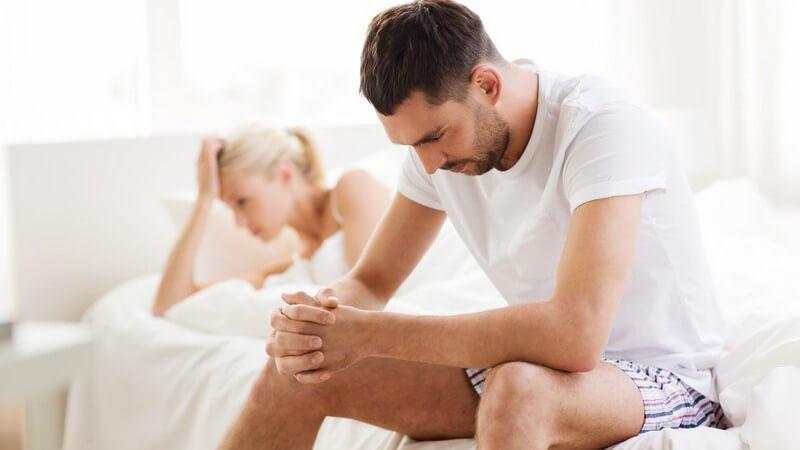 Paar enttäuscht oder zerstritten im Schlafzimmer, sie liegt auf die Hand gestützt im Bett, er sitzt auf der Bettkante
