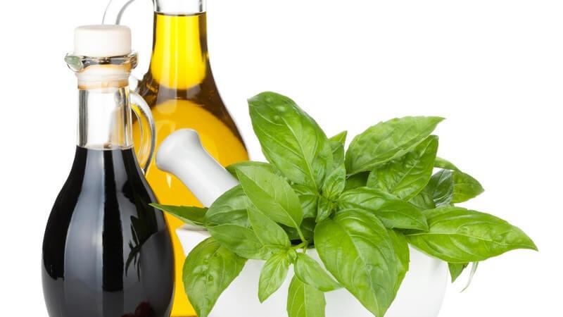 Öl- und Essigflasche neben Basilikum und Tomaten vor weißem Hintergrund
