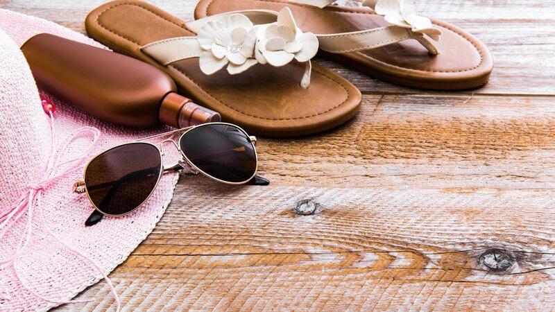 Sonnenhut, Sonnenbrille, Sonnencreme und Flip-Flops auf Holzuntergrund