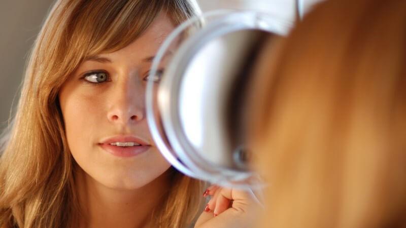 Mädchen blickt in einen kleinen Kosmetikspiegel