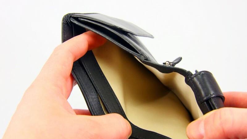 Hände, die das leere Scheinfach eines schwarzen Portemonnaies öffnen