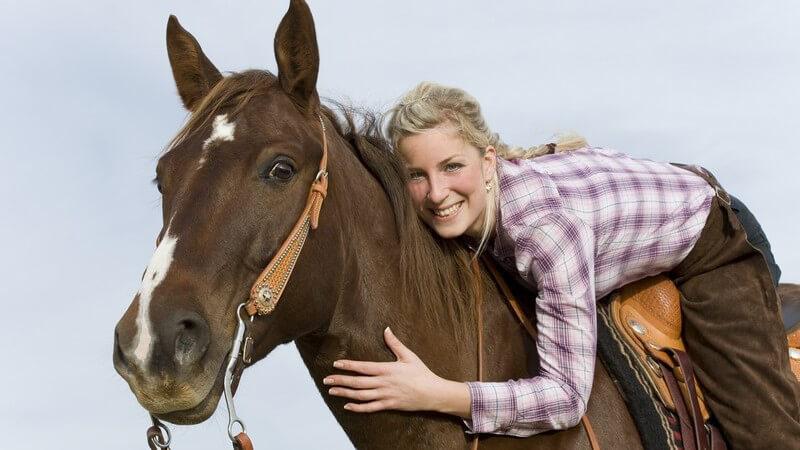 Junge Frau sitzt im Sattel und umarmt ihr Pferd
