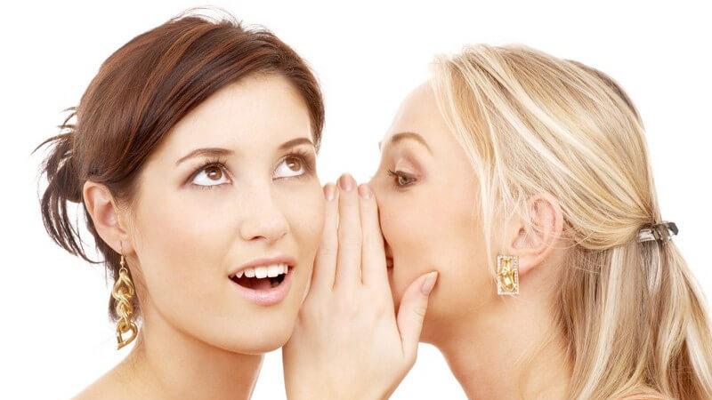Blonde Frau flüstert ihrer Freundin etwas ins Ohr