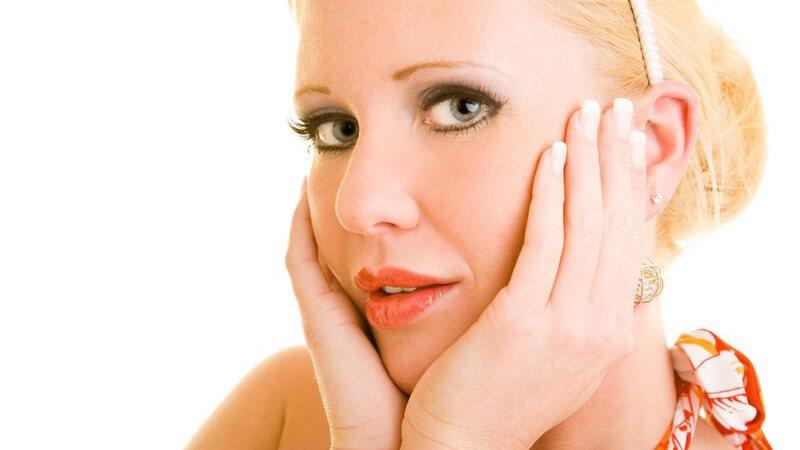 Blonde Frau mit Haarreif hält sich beide Hände ans Gesicht