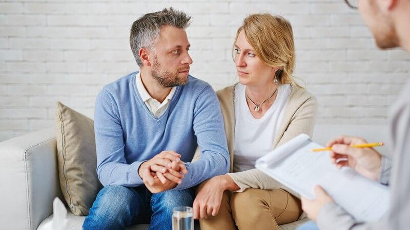 Trauriges Paar mittleren Alters sitzt händchenhaltend bei einem Psychologen auf der Couch