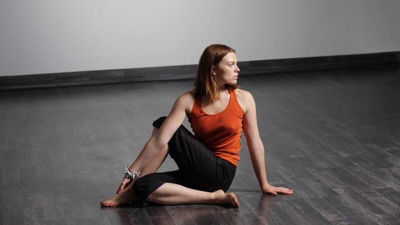 Junge Frau auf dunklem Holzboden bei Yogaübung