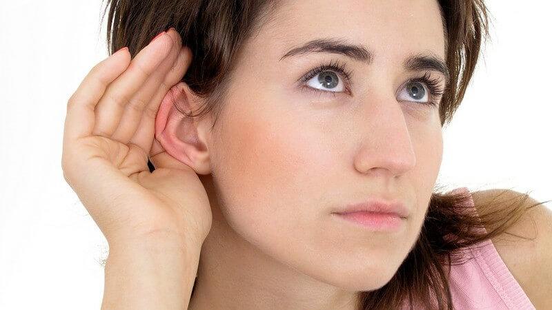 Junge Frau hält Hand hinters Ohr um besser zu hören, weißer Hintergrund