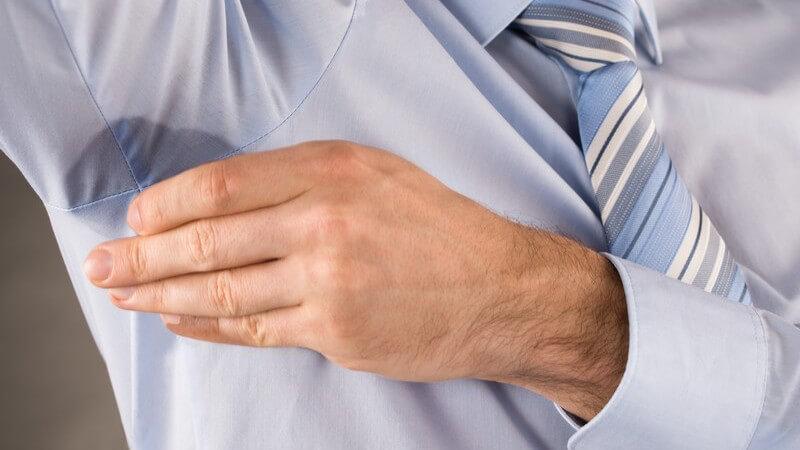 Geschäftsmann in blauem Hemd und Krawatte mit Schweißfleck unter dem rechten Arm