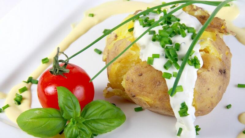 Kartoffeln mit Quark und Tomate auf weißem Teller serviert