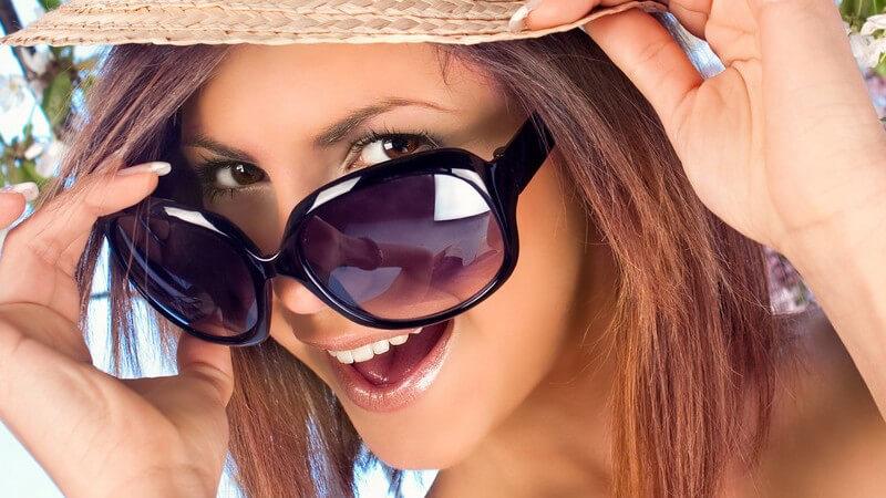 Junge Frau mit großer Sonnenbrille und Strohhut