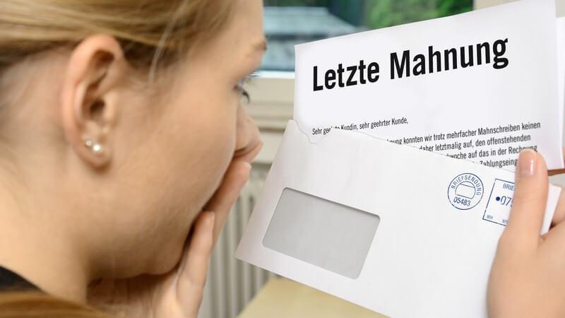 Frau hält erschrocken die Hand vor den Mund und betrachtet einen geöffnetes Brief mit einer Letzten Mahnung