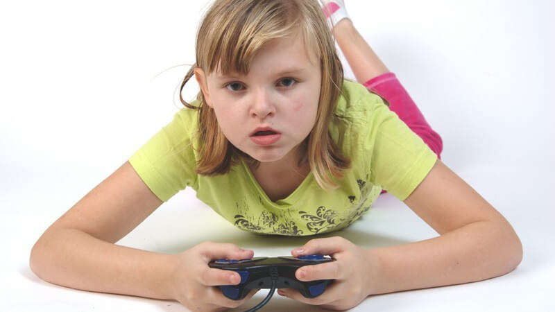 Mädchen liegt auf dem Bauch und hält Controller in den Händen, spielt Konsole