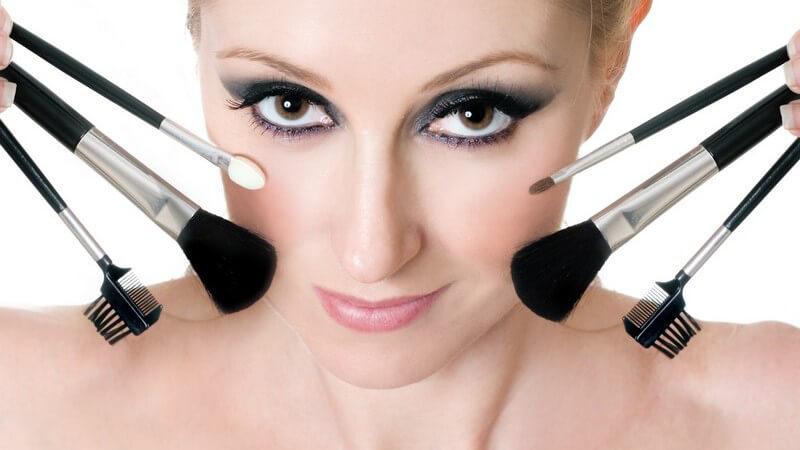 Geschminktes Frauengesicht, an den Seiten Make-up Pinsel und Applikatoren