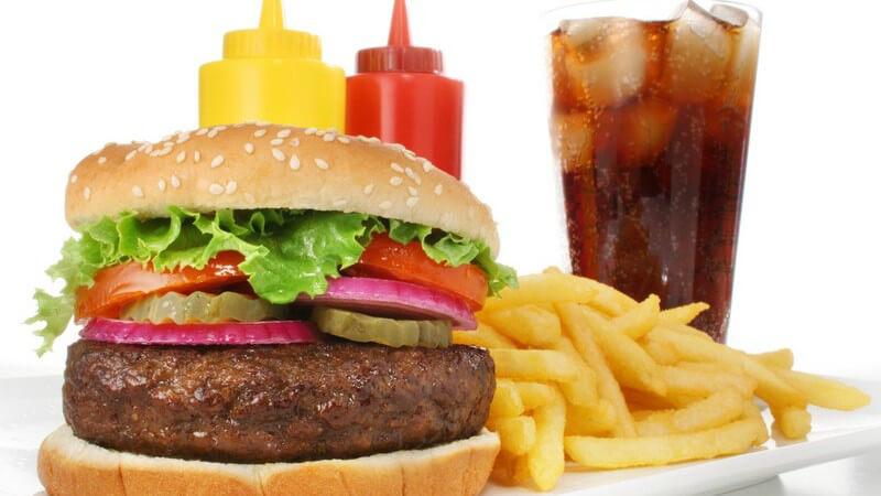 Hamburger mit Pommes, dahinter Ketchup, Mayonnaise und ein Glas mit Cola