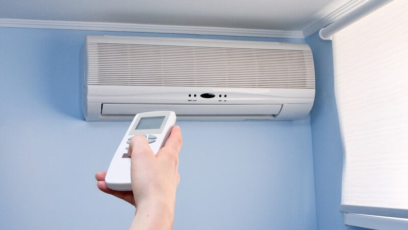 Hand hält Fernbedienung in Richtung Klimaanlage