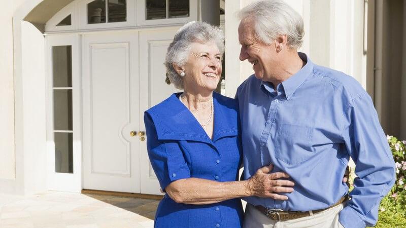 Senioren Paar steht lächelnd Arm in Arm vor Haus