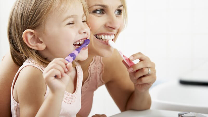 Mutter und Tochter stehen gemeinsam am Waschbecken und putzen sich die Zähne