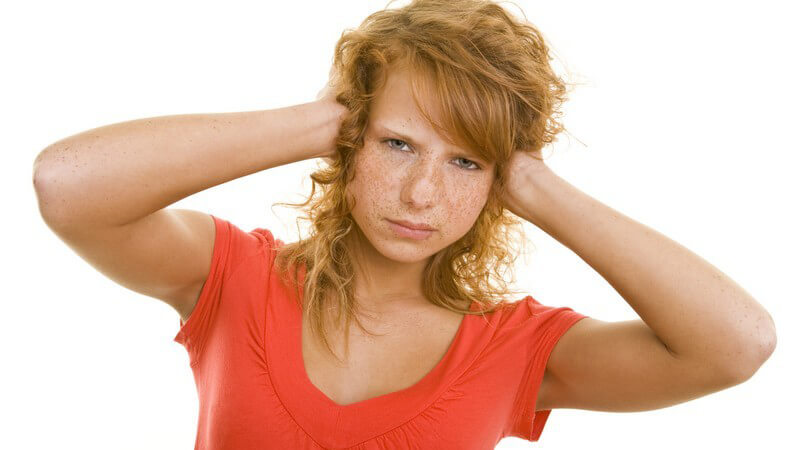 Junge Frau mit rotem Lockenkopf und Sommersprossen hält sich genervt die Ohren zu