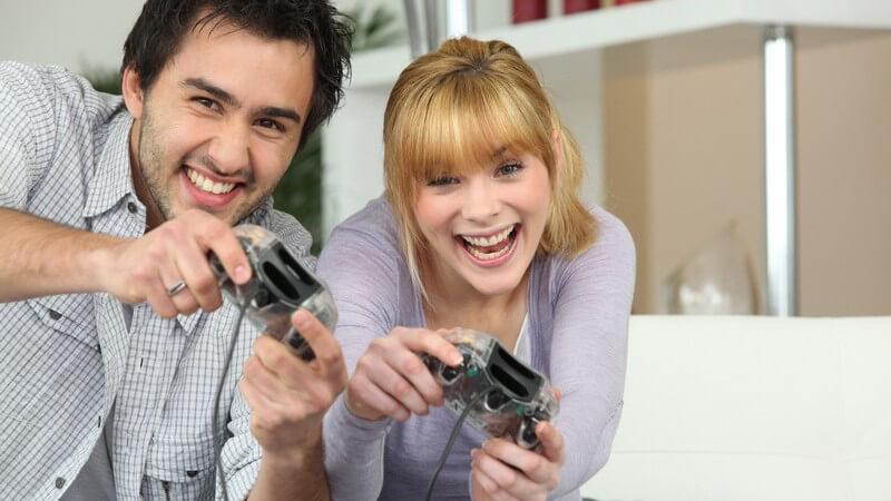 Junger Mann und Frau haben Spaß beim Videospiel, haben beide Controller in den Händen