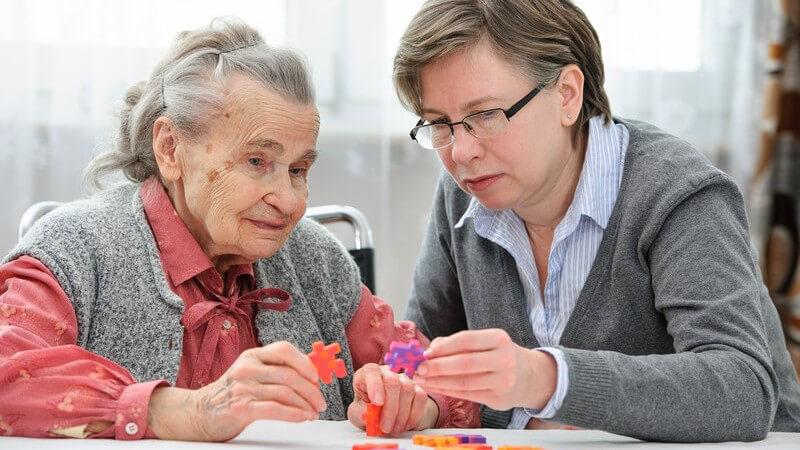 Gedächtnistraining im Altenheim - Seniorin mit Altenpflegerin oder Tochter beim Puzzeln