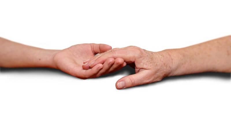 Junge und alte Hand fassen ineinander