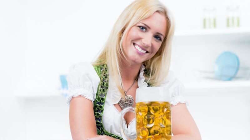 Blonde Frau in grünem Dirndl sitzt vor einem Maß Bier und lächelt