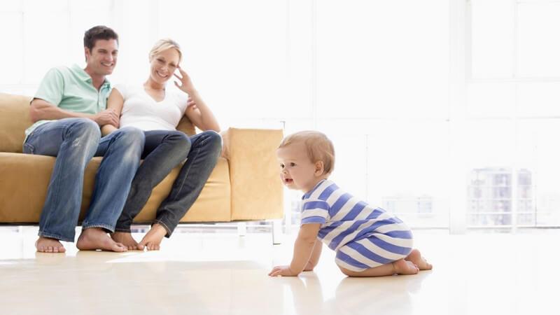 Junges Paar sitzt auf Couch, davor ihr Baby auf allen Vieren