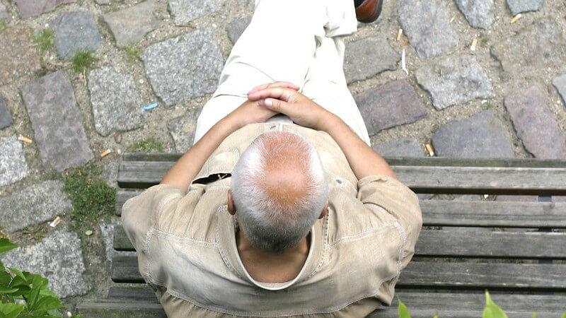 Ansicht von oben: Alter Mann sitzt allein auf Holzbank auf Kopfsteinpflaster