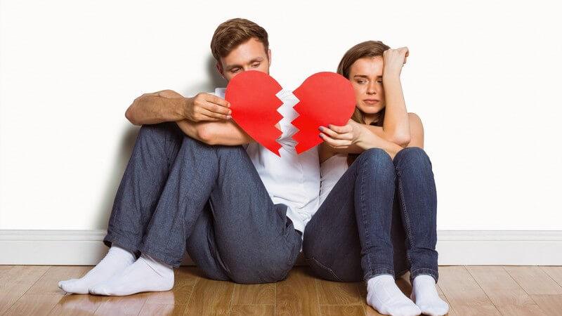 Junges Paar sitzt auf dem Boden und hält ein zerbrochenes Herz in den Händen
