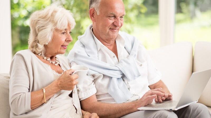 Altes Ehepaar sitzt auf der Couch, sie hält eine Tasse, er einen Laptop