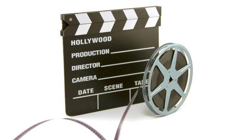Filmklappe und Filmrolle auf weißem Hintergrund