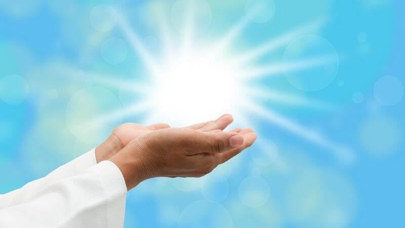 Offene, betende Hände unter der Sonne bei blauem Himmel