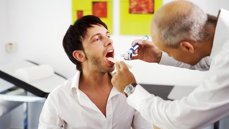 Arzt guckt jungem Mann in den Mund