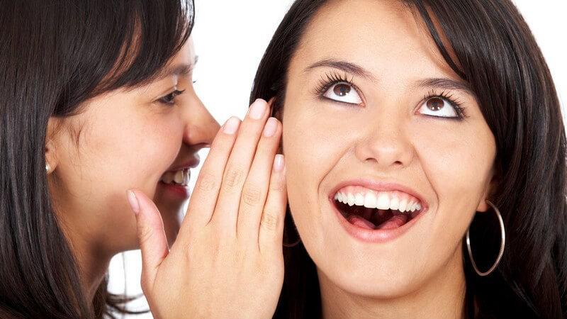 Zwei Freundinnen, eine flüstert der anderen etwas ins Ohr
