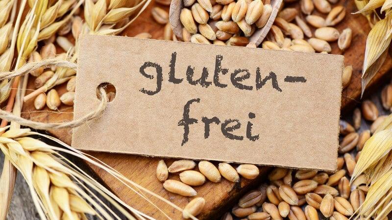 """Papierschild mit der Aufschrift """"glutenfrei"""" zwischen Weizenähren und -körnern"""