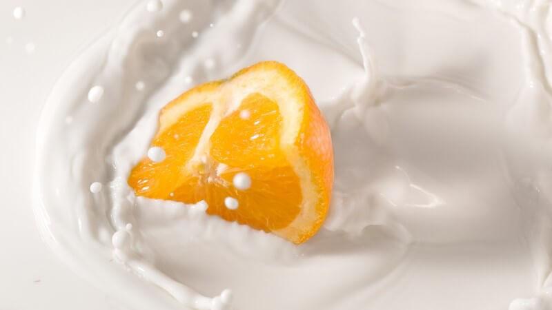 Stück frische Orange fällt in Milch