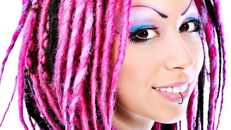 Gesichtsportrait junge Frau mit Labret Piercing und pinken Dreads