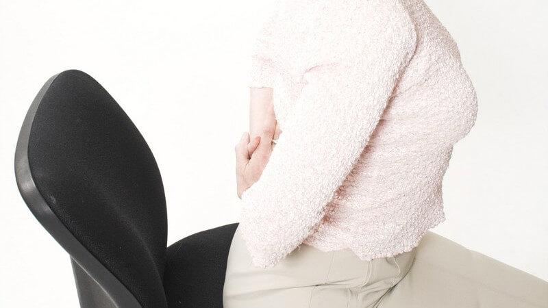 Seitenansicht Frau auf Bürostuhl macht Hohlkreuz, Rückenschmerzen