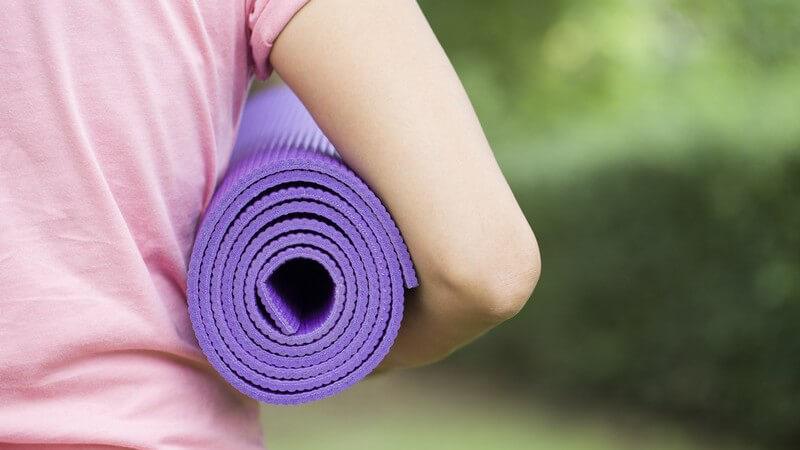 Frau in rosa Shirt trägt eine lila Yogamatte unter dem Arm