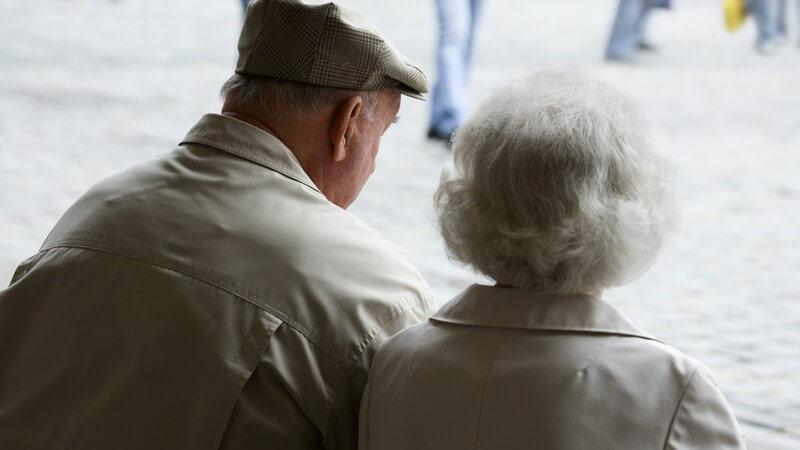 Rückansicht Rentnerpaar sitzt draußen auf Bank
