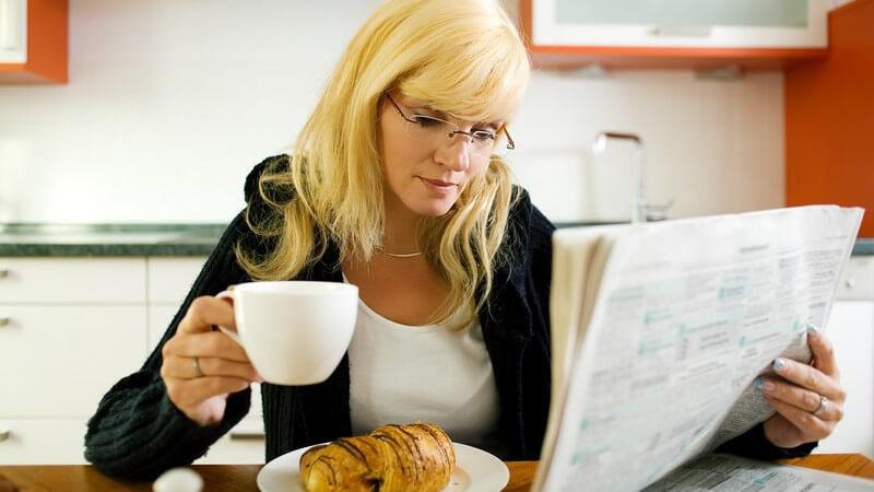 Frühstück blonde Frau, Brille, in Küche, in rechter Hand Kaffeetasse, in linker Tageszeitung, vor ihr Schokocroissant