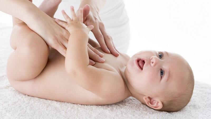 Nacktes Baby auf dem Rücken, Mutter massiert seine Brust