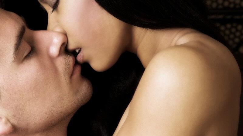 Nacktes Paar beim Küssen, er umarmt sie und verdeckt ihre Brust