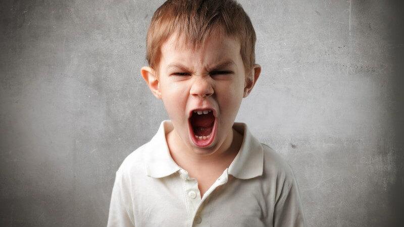 Kleiner Junge in weißem Poloshirt steht vor einer grauen Wand und schreit wütend